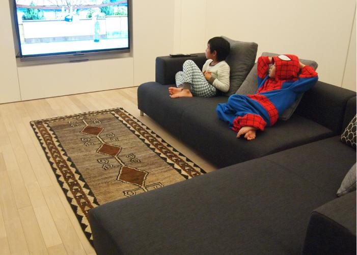 ソファの上でテレビを見る子供たち