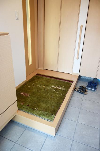 玄関に緑色のアートギャッベ