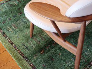 椅子の下の緑色のギャッベ