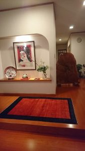 玄関に絵画と赤いアートギャッベ