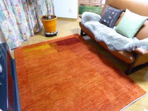 ソファ前のオレンジ色のギャッベ